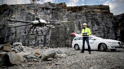 A workers steers a drone from the rocky ground, with his car in the background. Photo/illustration: Erik Mårtensson
