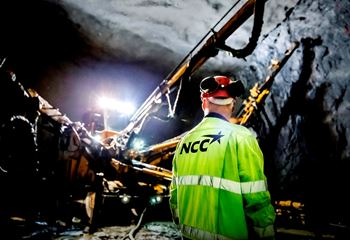 Inside a tunnel cave, a worker looks at machinery drilling and measuring against the cave wall. Photo/illustration: Conny Sillén