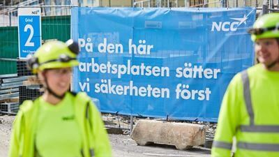 "Two workers in the foreground. The text in the background says ""at this workplace, we put safety first"". Photo/illustration: Joakim Kröger"