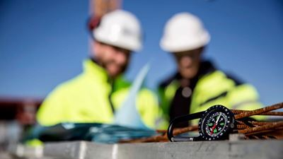 A compass in the foreground, with two workers in the background. Photo/illustration: Erik Mårtensson