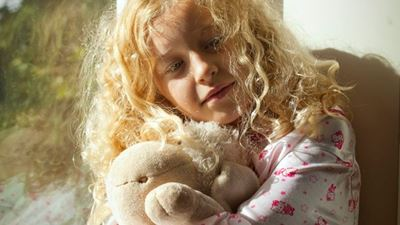 A child leans against a window while holding a bear. Photo/illustration: N/A